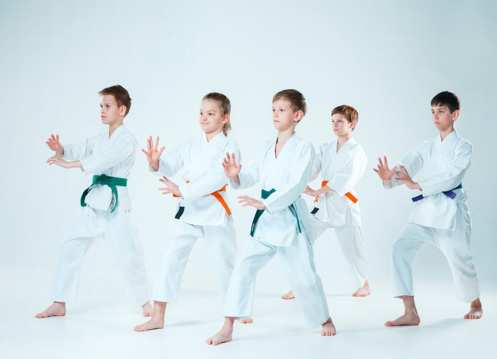 The group of boys and girl fighting at Aikido training